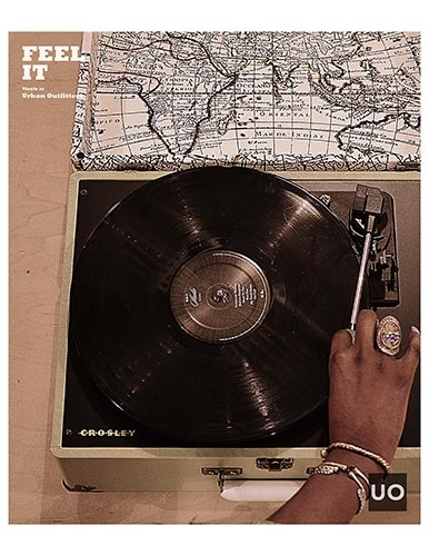"""A hand lifting the needle on a turntable with the headline """"Feel It."""""""