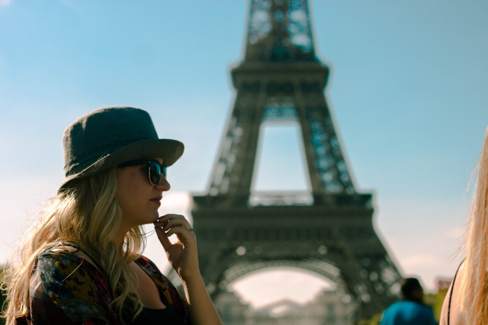 A student with the Eiffel Tower in Paris in back of her.