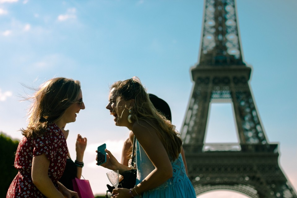 Two students talk with the Eiffel Tower in Paris in back of them.