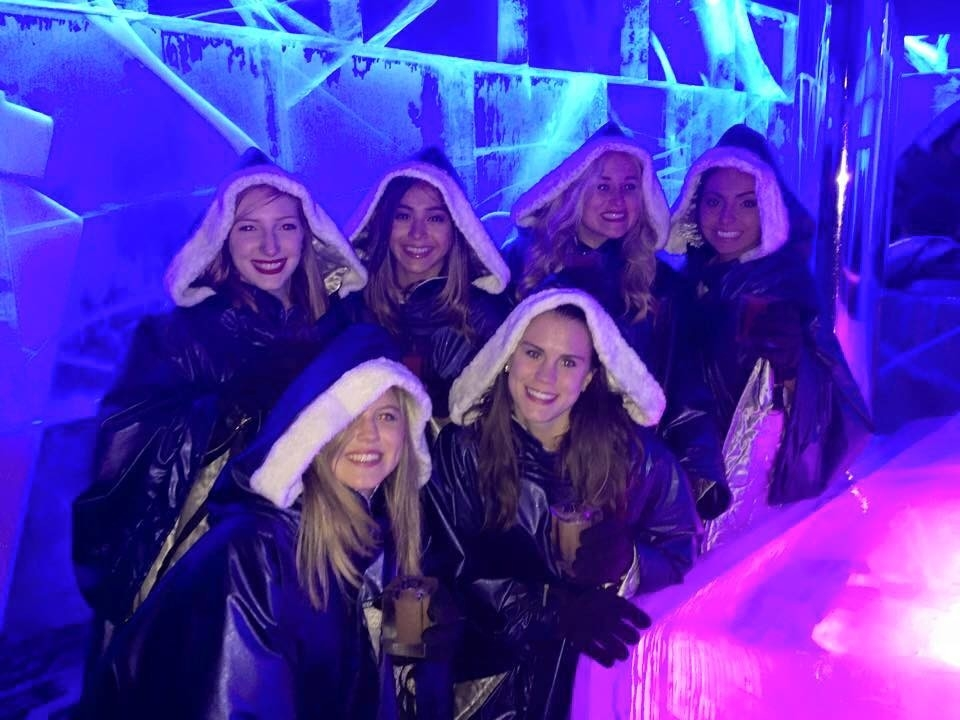 Students in an ice bar, wearing coats.