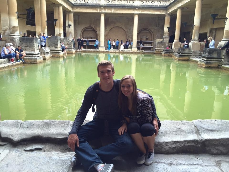 Students sitting at the edge of a historic bath.