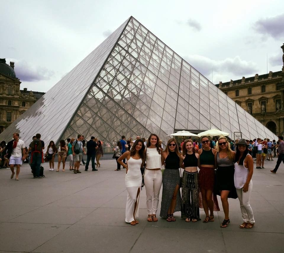 Students in front of the glass pyramid at the Louvre in Paris.
