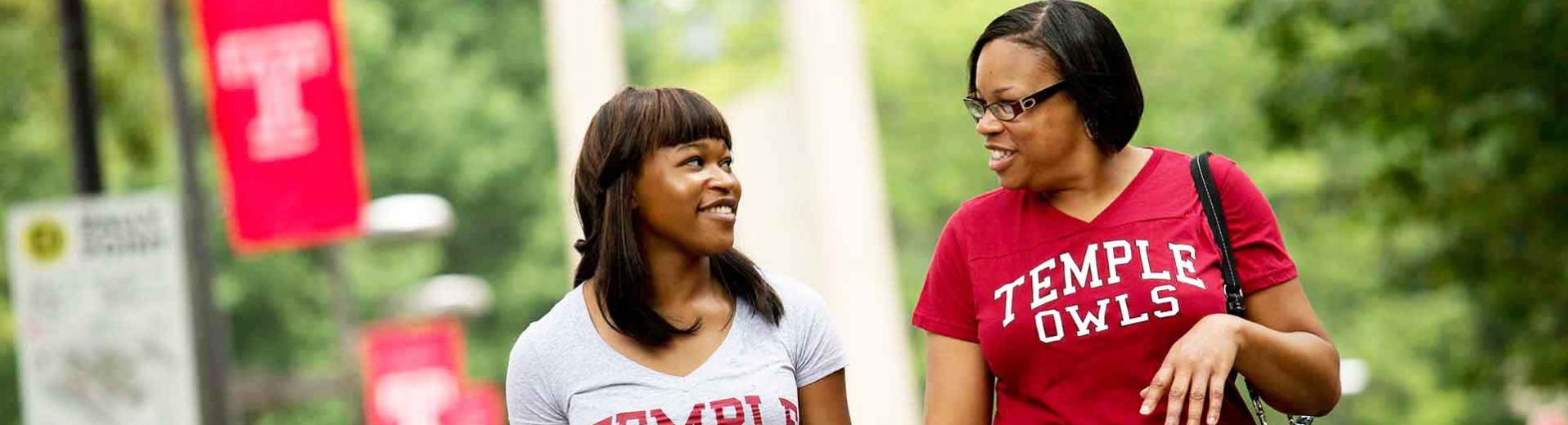 A daughter and her mother smile at each other while walking across campus.