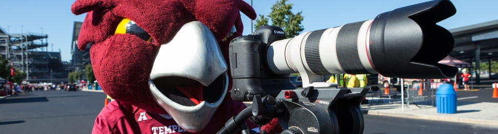 Hooter the owl mascot holding a camera