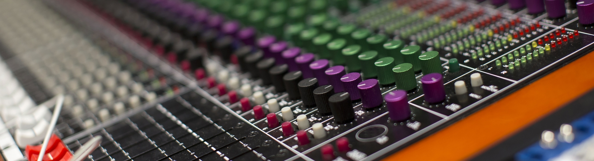 close up of sound board with multiple colored controls and knobs