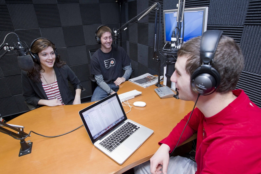 Radio broadcast room with one male student host along with a fellow female and male student