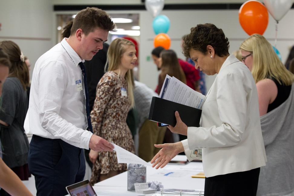 A student standing behind a table displays his portfolio at a career fair.