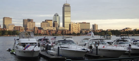 boats lined up in a harbor with the Boston skyline in the background