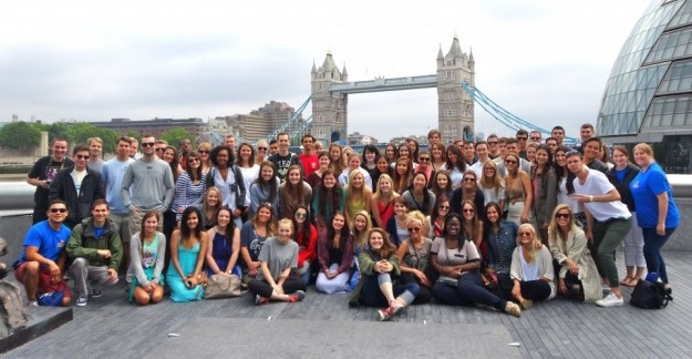 a group of students, staff and tour guides from a London bus tour
