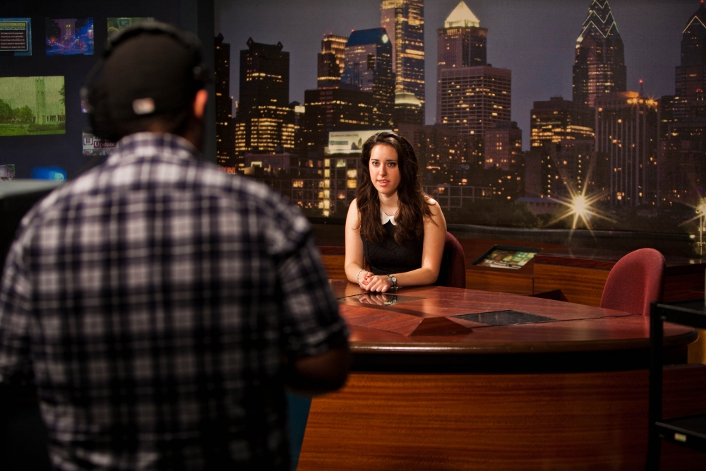 Female student at TUTV anchor desk during auditions and a cameraman is in the foreground